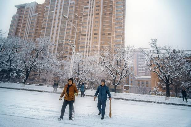 After an overnight snowfall, families and residents take to the streets on a Sunday morning with improvised shovels. North Koreans take their civic duty seriously – everyone pitches in – lending streets like this the air of a city-wide social gathering. Despite few snowplows, major roadways and public spaces are always clear by noon.
