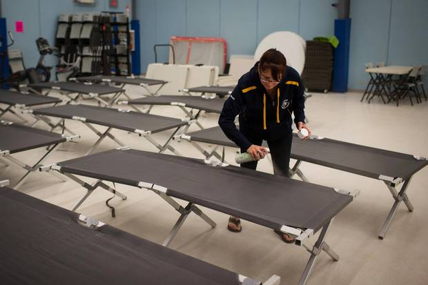 Wendy Tremblay prepares cots for residents of Fort McMurray as they prepare to assemble in Conklin, Alta.