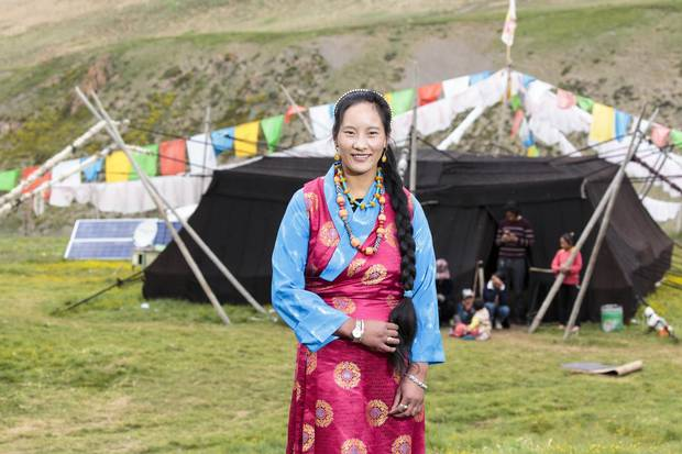 Leray's daughter poses in her traditional Tibetan clothing in front of her family's black yak wool tent.