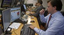Traders monitor computer screens in a bank in Lisbon Jan. 23, 2013. Portuguese debt yields fell on Wednesday with investors heartened by strong demand at a five-year debt sale marking the country's first foray into bond markets since its 2011 bailout. (JOSE MANUEL RIBEIRO/REUTERS)