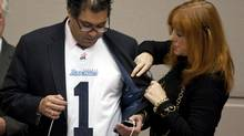 Alderman Diane Colley-Urquhart, right, inspects Calgary Mayor Naheed Nenshi's Toronto Argonauts jersey as he meets with council Calgary, Alta., Tuesday, Nov. 27, 2012. Nenshi had to wear the jersey after losing a bet when the Calgary Stampeders lost the Grey Cup to the Toronto Argonauts. (Jeff McIntosh/THE CANADIAN PRESS)