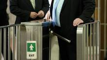 Federal Finance Minister Jim Flaherty, left, and Toronto Mayor Rob Ford go through a turnstile on their way to announcing funding of a subway line extension in Toronto on Monday September 23, 2013. (Frank Gunn/THE CANADIAN PRESS)