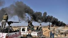 Smoke billows as Libyan rebels progress westward from the town of Bin Jawad towards Moammar Gadhafi's hom town of Sirte on March 28, 2011. (ARIS MESSINIS/ARIS MESSINIS/AFP/Getty Images)
