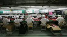 Workers are seen inside a Foxconn factory in the township of Longhua in the southern Guangdong province on May 26, 2010. Foxconn assembles electronics equipment for several global companies, including Apple. (BOBBY YIP/BOBBY YIP/REUTERS)