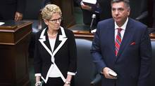 Ontario Premier Kathleen Wynne is sworn in alongside Liberal MPP Charles Sousa during a swearing in ceremony at Queen's Park in Toronto on Wednesday, July 2, 2014. (Aaron Vincent Elkaim/THE CANADIAN PRESS)