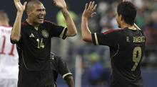 Mexico's Jorge Enriquez (L) congratulates teammate Raul Jimenez (R) after Jimenez scored a goal during their CONCACAF Gold Cup soccer match against Canada in Seattle, Washington July 11, 2013. (MARCUS DONNER/REUTERS)