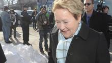Pauline Marois walks past a group of housing protesters in Montreal during a campaign stop on Tuesday, March 18, 2014. (Ryan Remiorz/THE CANADIAN PRESS)