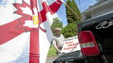 Matthew Glenn, president of the New Brunswick Anglo Society, loads protest signs into his truck at his home in Minto. the town has just voted to give prominence to French on commercial signs. (Michael David Smith/Michael David Smith)