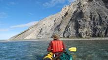 A canoeist paddles along the Wind River, one of the waterways that defines the Peel River watershed a ther northern end of the Rocky and Mackenzie Mountain Chain. (Jill Pangman/Peel River Watershed)