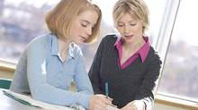 A businesswoman talks to intern about paperwork. (Hemera Technologies/Getty Images)