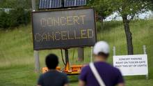 People read an information sign after a stage collapsed leaving one person dead and others injured after the main stage partially collapsed before a Radiohead concert at Downsview Park in Toronto on Saturday, June 16, 2012. (Nathan Denette/CP)