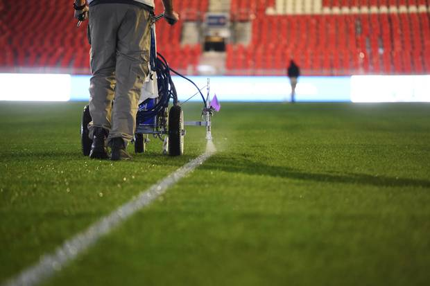 The ground crew works late into the night measuring and painting lines on the field.