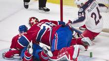 Columbus Blue Jackets' Derek MacKenzie, right, scores against Montreal Canadiens goaltender Carey Price, centre as Canadiens' P.K. Subban defends during first period NHL hockey action in Montreal, Thursday, March 20, 2014. (Graham Hughes/THE CANADIAN PRESS)