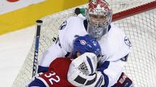 Montreal Canadiens' Mark Streit, from Switzerland, gets a glove in the face after sliding into Tampa Bay Lightning goaltender Karri Ramo during first period NHL hockey action Thursday, Jan. 3, 2008 in Montreal. (Paul Chiasson/The Canadian Press)