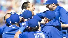 Toronto Blue Jays Munenori Kawasaki (C) is mobbed by team mates after he hit a game winning double in the ninth inning of their American League baseball game against the Baltimore Orioles in Toronto May 26, 2013. (FRED THORNHILL/REUTERS)