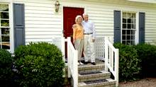 Retired couple in front of their house. (Photos.com)