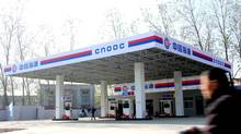 A cyclist rides past a gas station of CNOOC (China National Offshore Oil Corporation) in Zhoukou city, central Chinas Henan province, in this file photo. (Hou wei zk/THE CANADIAN PRESS)