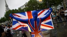 A man holds a British flag in downtown London during a clock countdown prior to the Opening Ceremony at the 2012 Summer Olympics, Friday, July 27, 2012, in London. (Sergey Ponomarev/AP)