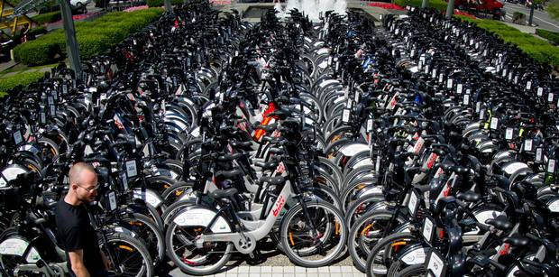 A PBSC Urban Solutions worker walks past hundreds of BIXI bikes parked outside the Sheraton Wall Centre for delegates of the Velo-city Global 2012 conference to use in Vancouver, B.C., on Monday June 25, 2012.