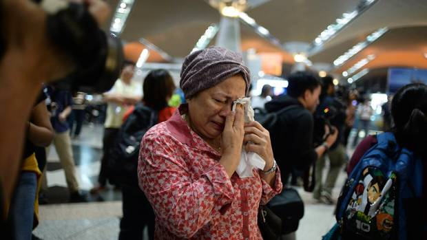 A woman reacts to news regarding a Malaysia Airlines plane that crashed in eastern Ukraine at Kuala Lumpur International Airport in Sepang, Malaysia, Friday, July 18, 2014. (JOSHUA PAUL/ASSOCIATED PRESS)