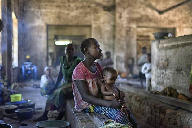 A displaced woman and her baby, from a forest-dwelling hunter-gatherer group in Congo, live in an abandoned factory in Nyunzu, Congo, March 22, 2016. Traditional forest dwellers, known for their capacity to cooperate, have become embroiled in and displaced by one of the conflicts that typify the Democratic Republic of Congo as an election crisis looms.