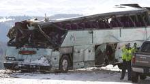 Tow truck operators work on tour bus that careened off a mountain highway and plunged down a snow-covered slope, killing nine passengers and injuring at least 27 others, in Oregon on Dec. 31, 2012. The charter bus was carrying about 40 people through the Blue Mountains of northern Oregon en route from Las Vegas to Vancouver, when it crashed through a guard rail on Interstate 84 on Sunday morning, authorities said. (STEVE DIPAOLA/REUTERS)
