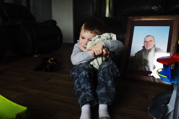 Casey Smith hugs his blanket in front of a photo of his late father, Cpl. Scott Smith.