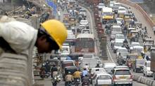 A worker leans over a wall as traffic comes to a standstill on a busy road in the southern Indian city of Hyderabad (STRINGER/INDIA)