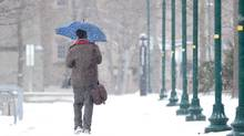 A man walks with an umbrella down a snow covered path at the University of Western Ontario in London, Ontario, January 2, 2012. (GEOFF ROBINS For The Globe and Mail/GEOFF ROBINS For The Globe and Mail)