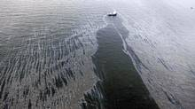 In this aerial photo taken in the Gulf of Mexico a boat with an oil boom tries to contain oil spilled from the explosion and collapse of the Deepwater Horizon oil rig. (Gerald Herbert/AP)