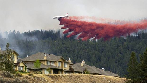 A water bomber drops a load.of fire retardant on Pinnacle Ridge in East Kelowna, B.C. on Sept. 7, 2003.