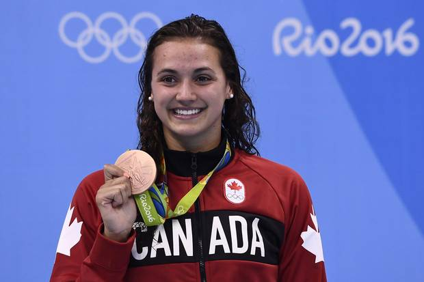 Canada's Kylie Masse poses with her bronze medal on the podium of the Women's 100-metre Backstroke at the Rio 2016 Olympic Games in Rio de Janeiro on August 8, 2016.