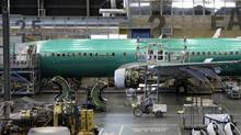 In this file photo taken June 3, 2011, an employee rides a tricycle past a Boeing 737 airplane at the company's assembly facility in Renton, Wash. (Ted S. Warren/AP)