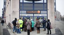 Customers wait outside a Swedbank AB branch in Malmoe. The escalation in Swedish household debt has gone hand in hand with house prices, which have increased threefold since 1995 as mortgage rates plunged from 10 per cent to 4 per cent. (Linus Hook/Bloomberg)