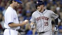 Houston Astros' Robbie Grossman rounds the bases after his two-run homer as Toronto Blue Jays pitcher R.A. Dickey makes his way back to the mound during fifth inning AL baseball action in Toronto on Thursday April 10, 2014. (Frank Gunn/THE CANADIAN PRESS)