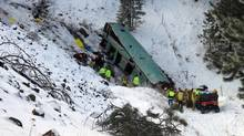 Emergency personnel respond to the scene of a fatal accident where a tour bus careened through a guardrail and several hundred feet down a steep embankment east of Pendleton, Ore., on Sunday. (TIM TRAINOR/ASSOCIATED PRESS)