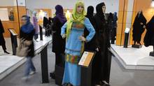 An Iranian woman walks past mannequins covered with Islamic clothing designed by Iranian designers during an Islamic fashion exhibition in central Tehran March 1, 2012. (MORTEZA NIKOUBAZL/REUTERS/Morteza Nikoubazl)