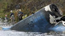 Rescuers work at the crash site of a Russian Yak-42 jet near the city of Yaroslavl, on the Volga River about 150 miles (240 kilometers) northeast of Moscow, Russia, Wednesday, Sept. 7, 2011. (Misha Japaridze/AP)