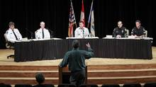 A local resident voices his concerns to the Port Moody mayor, as well as city and Vancouver police officers, during a rally against gun violence at Port Moody city hall on Monday. (JEFF VINNICK/THE GLOBE AND MAIL)