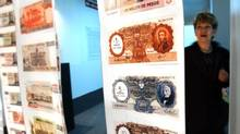 A woman examines old currency in the Foreign Debt Museum in Buenos Aires in this file photo. (NATACHA PISARENKO/AP)