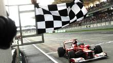 Ferrari Formula One driver Fernando Alonso of Spain celebrates as he gets the chequered flag at the Malaysian Formula One Grand Prix at Sepang, Malaysia, Sunday, March 25, 2012. (Dita Alangkara/AP Photo)