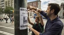 Whitney Brown and Andrew O'Sullivan from the Pivot Legal Society hang wanted posters of George Wolsey at Main and Hastings streets in Vancouver September 4, 2013. (John Lehmann/The Globe and Mail)