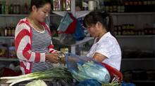 A Chinese woman pays for vegetables at a store in Changping, on the outskirts of Beijing, Aug. 9, 2012. (Andy Wong/AP)