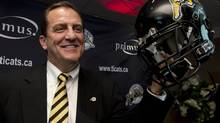 Kent Austin holds up a team helmet at a news conference introducing him as Hamilton Tiger-Cats head coach on Monday, Dec.17, 2012. (Frank Gunn/THE CANADIAN PRESS)