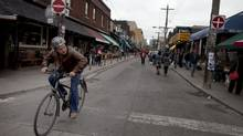 A cyclist passes through Toronto's Kensington Market on June 7, 2013. (MOE DOIRON/THE GLOBE AND MAIL)