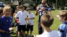 Toronto Argonauts Chris Van Zeyl talks at Rosedale Field to a group of kids from the neighbourhood who attended the commemoration of the first Grey Cup played at the field in 1909, Toronto May 30 2012. (Fernando Morales/The Globe and Mail)