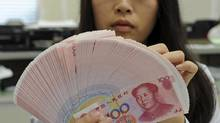 An employee counts Chinese yuan notes inside a bank in Taipei. (REUTERS)