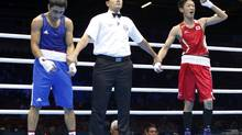 Azerbaijan's Magomed Abdulhamidov (L) waits for the decision in his fight against Japan's Satoshi Shimizu (R) in their Men's Bantam (56kg) Round of 16 boxing match during the London 2012 Olympic Games August 1, 2012. (MURAD SEZER/REUTERS)