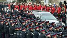 Police officers line up as the hearse carrying the casket of Const. Jennifer Kovach drives along the funeral route in Guelph, Ont., on Thursday, March 21, 2013. (Nathan Denette/THE CANADIAN PRESS)