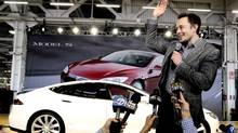 In this June 22, 2012 file photo, Tesla CEO Elon Musk waves during a rally at the Tesla factory in Fremont, Calif. (Paul Sakuma/AP Photo)